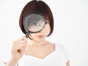 虫眼鏡を覗いている女性の画像